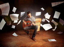 Homem novo que joga a guitarra com voo da partitura em torno dele Fotos de Stock Royalty Free