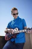 Homem novo que joga a guitarra elétrica fotografia de stock