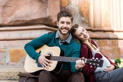 homem novo que joga a guitarra para a esposa grávida ao descansar fotos de stock