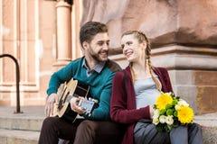 homem novo que joga a guitarra para a esposa grávida ao descansar foto de stock