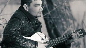 Homem novo que joga a guitarra perto do b&w do rio filme