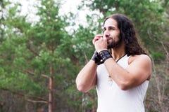 Homem novo que joga a harmônica em uma clareira da floresta foto de stock royalty free