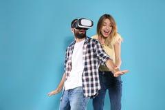 Homem novo que joga jogos de vídeo com auriculares de VR e a mulher emocional imagem de stock royalty free