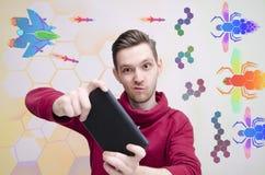 Homem novo que joga jogos de vídeo em sua tabuleta imagens de stock