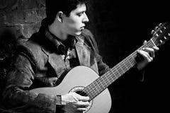 Homem novo que joga na guitarra Imagens de Stock
