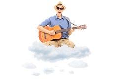 Homem novo que joga na guitarra acústica e que flutua em nuvens Foto de Stock Royalty Free