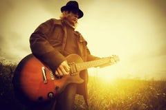 Homem novo que joga na guitarra fora vintage Imagens de Stock Royalty Free
