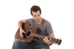 Homem novo que joga o assento da guitarra acústica Fotos de Stock