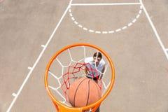 Homem novo que joga o basquetebol com a bola na rede Fotos de Stock Royalty Free