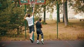 Homem novo que joga o basquetebol na terra de esportes com amigo - pingando, evitando seu oponente e jogando uma bola - video estoque