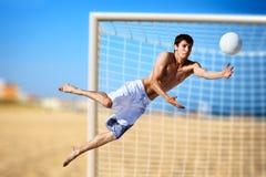 Homem novo que joga o futebol Fotografia de Stock Royalty Free