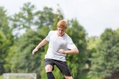 Homem novo que joga o futebol - fazendo um movimento do futebol Imagem de Stock Royalty Free