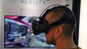 Homem novo que joga o jogo do atirador da realidade virtual em auriculares dos vidros de VR Conceito futuro da tecnologia 4K Bang video estoque