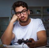 Homem novo que joga o muito tempo dos jogos tarde no escrit?rio imagens de stock royalty free