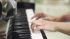 Homem novo que joga o piano As mãos fecham-se acima E Instrumento musical do teclado r r filme