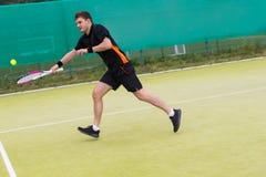 Homem novo que joga o tênis na corte de grama do tênis no amanhecer Fotografia de Stock