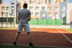Homem novo que joga o tênis na corte do pátio traseiro da escola foto de stock royalty free