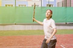 Homem novo que joga o tênis no tiro de fatura exterior da corte imagem de stock