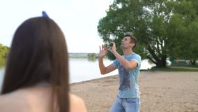 Homem novo que joga o voleibol em um Sandy Beach perto de um lago O indivíduo e a menina jogam com uma bola perto da água video estoque