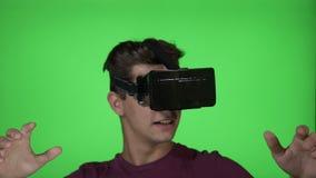 Homem novo que joga um jogo da aventura do horror usando uns auriculares da realidade virtual de VR no fundo da chave do croma - vídeos de arquivo
