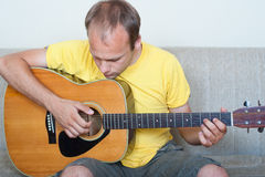 Homem novo que joga uma guitarra Foto de Stock