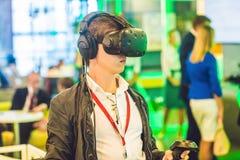 Homem novo que joga vidros da realidade virtual dos jogos de vídeo cheerful imagens de stock