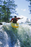 Homem novo que kayaking na cachoeira Fotos de Stock