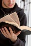 A Bíblia da leitura do homem Imagens de Stock