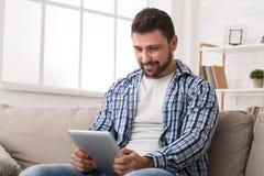 Homem novo que lê o artigo em linha na tabuleta digital fotos de stock royalty free