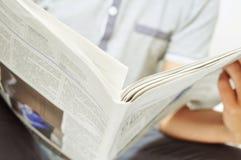 Homem novo que lê o jornal foto de stock royalty free