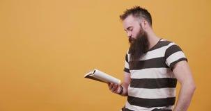 Homem novo que lê silenciosamente um livro e para acariciar seus barba e bigode video estoque