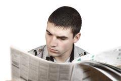 Homem novo que lê um jornal fotos de stock royalty free