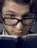Homem novo que lê um livro Fotos de Stock Royalty Free