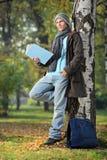 Homem novo que lê um livro Fotografia de Stock Royalty Free