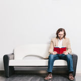 Homem novo que lê um livro imagens de stock royalty free