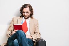 Homem novo que lê um livro foto de stock