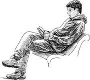 Homem novo que lê um livro Imagens de Stock