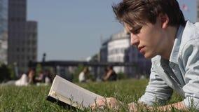 Homem novo que lê um livro ao ar livre filme