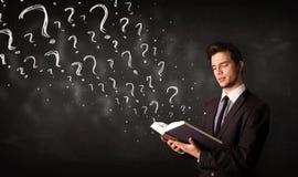 Homem novo que lê um livro com os pontos de interrogação que saem dele fotos de stock