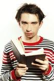Homem novo que lê um livro em um fundo branco Imagens de Stock