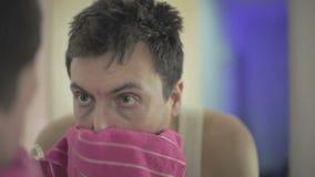 Homem novo que lava suas cara e limpezas sua cara com uma toalha na frente do espelho vídeos de arquivo