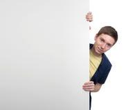 Homem novo que levanta ao lado de uma bandeira Foto de Stock