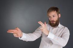 Homem novo que levanta com dedo-armas Fotos de Stock Royalty Free