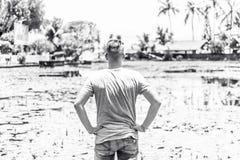 Homem novo que levanta no campo de flor dos lótus no lago, ilha tropical de Bali, Indonésia Retrato preto e branco Imagem de Stock Royalty Free