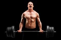 Homem novo que levanta um peso pesado Fotografia de Stock Royalty Free