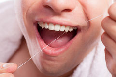 Homem novo que limpa seus dentes brancos com o fio dental foto de stock royalty free