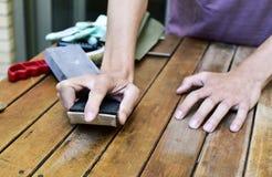 Homem novo que lixa uma tabela de madeira com um bloco de lixamento Imagens de Stock