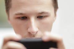 Homem novo que lokking na tela do telemóvel Imagens de Stock Royalty Free