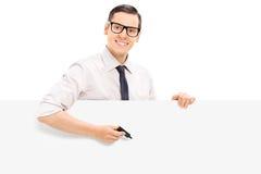 Homem novo que mantém o marcador contra um painel vazio Imagem de Stock