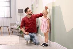 Homem novo que mede sua altura do ` s da filha fotografia de stock royalty free